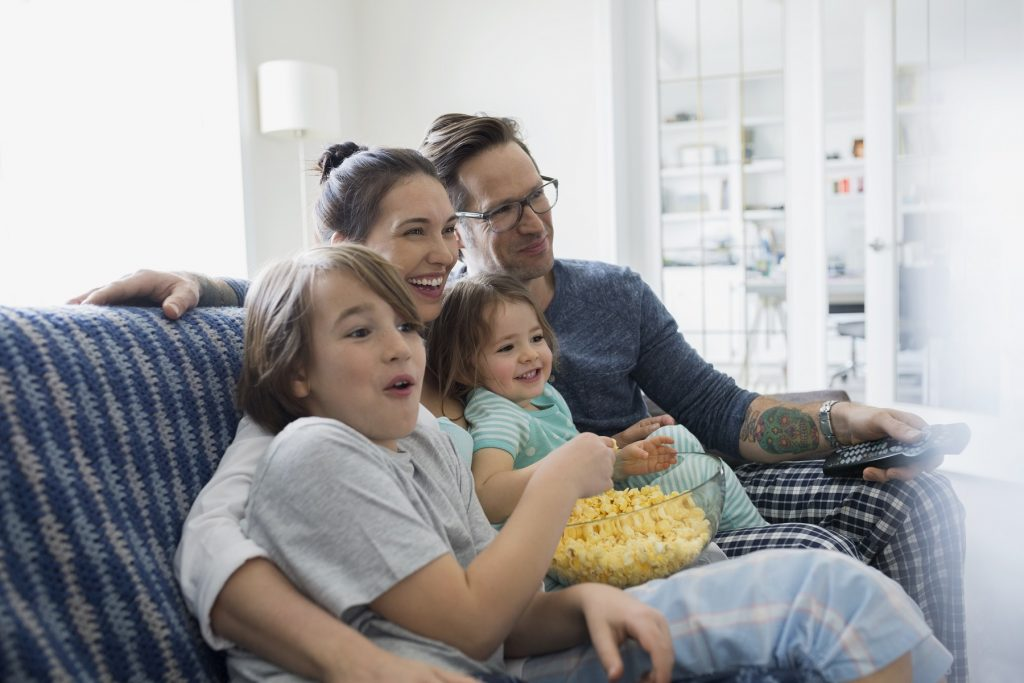 Family in pajamas watching TV and eating popcorn